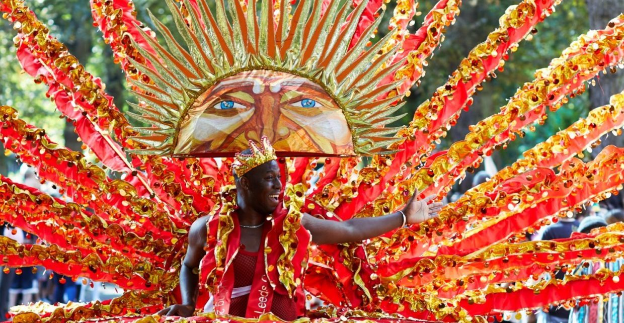 A photo of a carnival participant dressed in a large, orange feathered costume