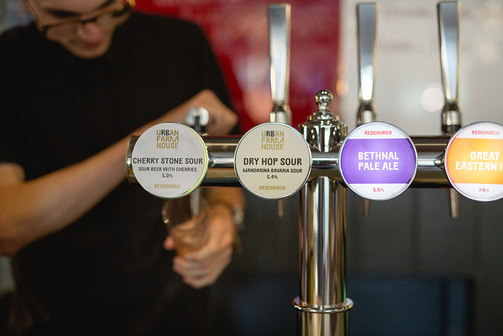 A bartender at a pub during Leeds Beer Week pulling a pint of beer from a tap.