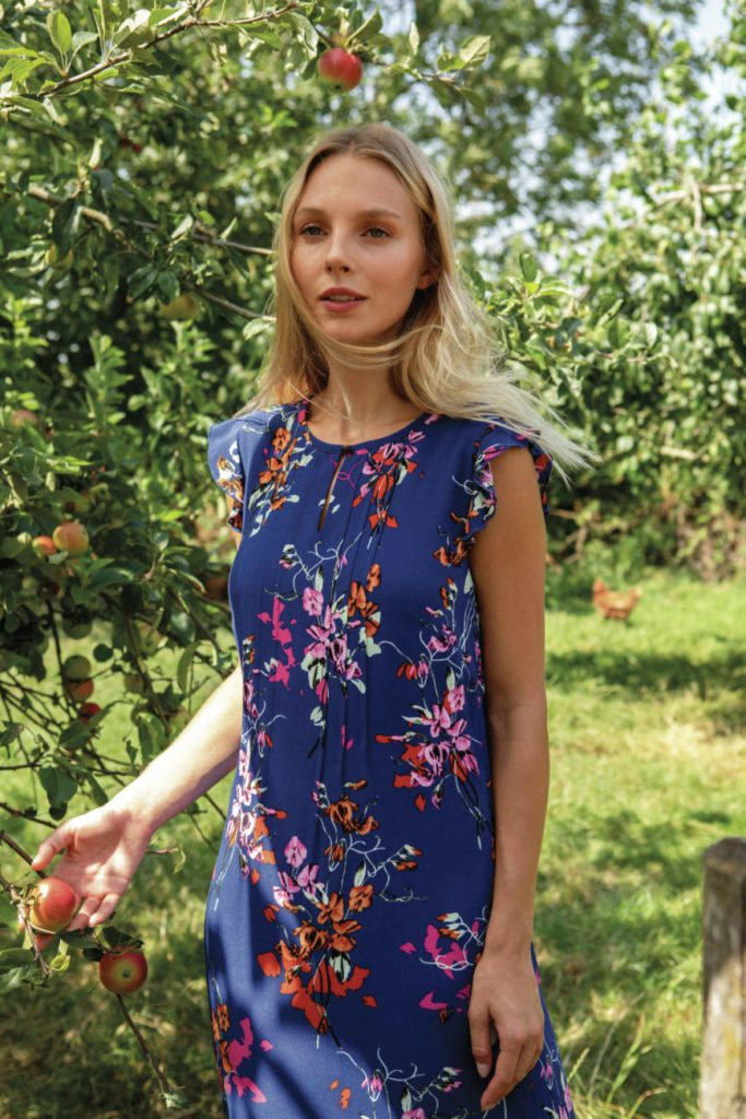 A Laura Ashley model poses in a blue dress with a flower pattern