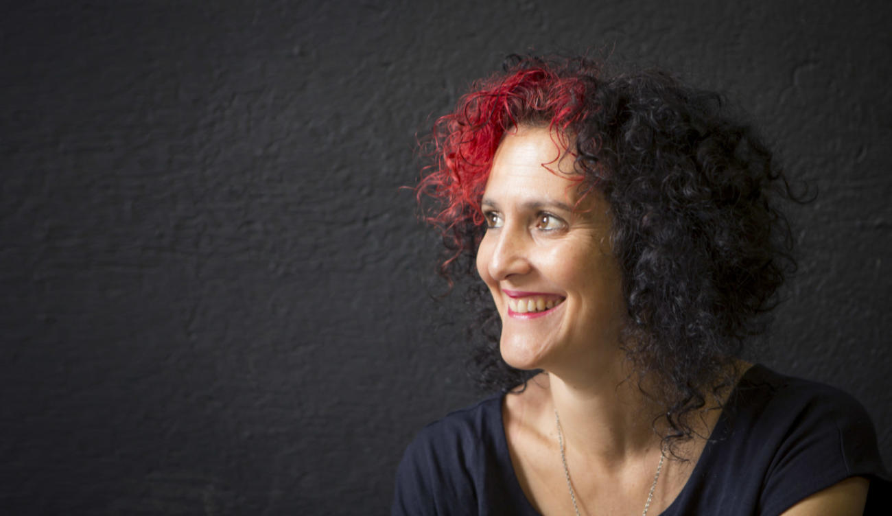 Side-on photo of Benita Matofska, author of Generation Share, against a black background